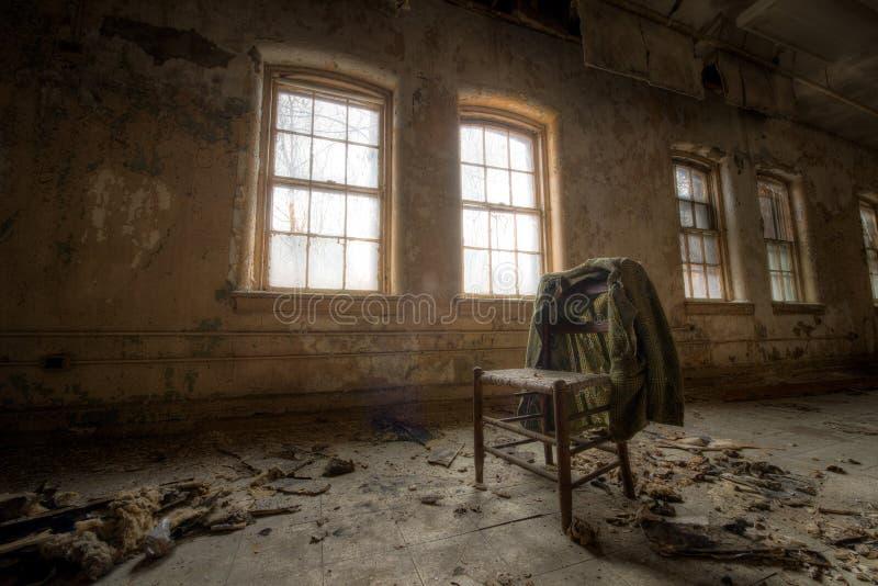 Alter Mantel und Stuhl in einem verlassenen Gebäude stockbild