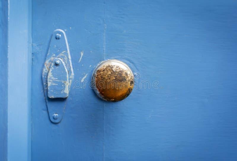 Alter Messingtürgriff auf einer gemalten blauen Tür lizenzfreie stockfotografie