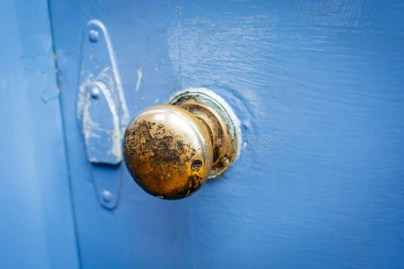 Alter Messingtürgriff auf einer gemalten blauen Tür lizenzfreies stockbild