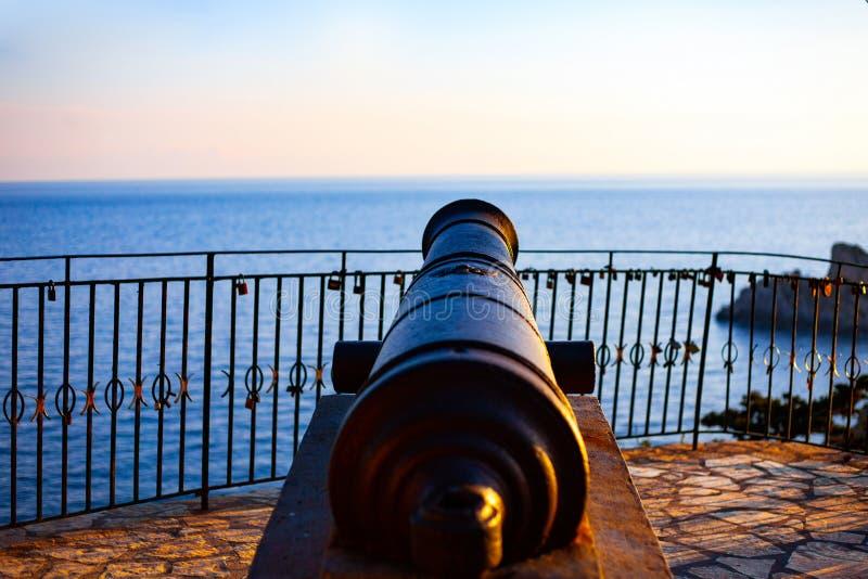 Alter Metallschlosskanon auf der Wand Antiker Eisenkanon auf der Küste Blauer Himmel über dem Meer lizenzfreies stockfoto