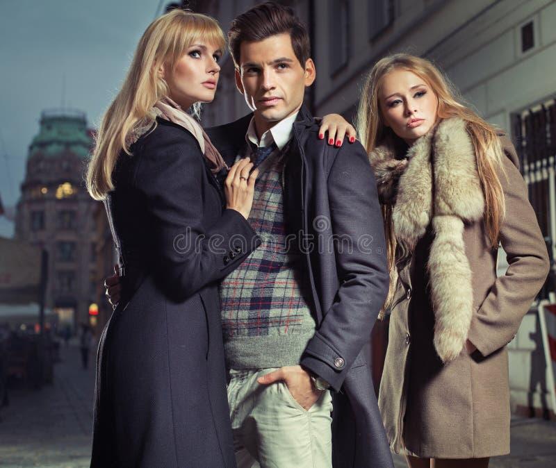 Alter Modemann mit Firma von zwei netten Frauen stockbild