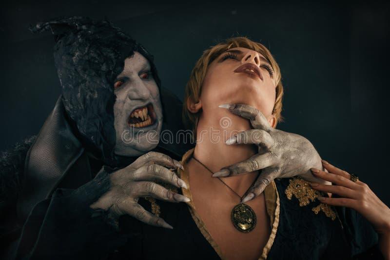 Alter Monstervampirsdämon beißt einen Frauenhals Halloween fant stockfotos