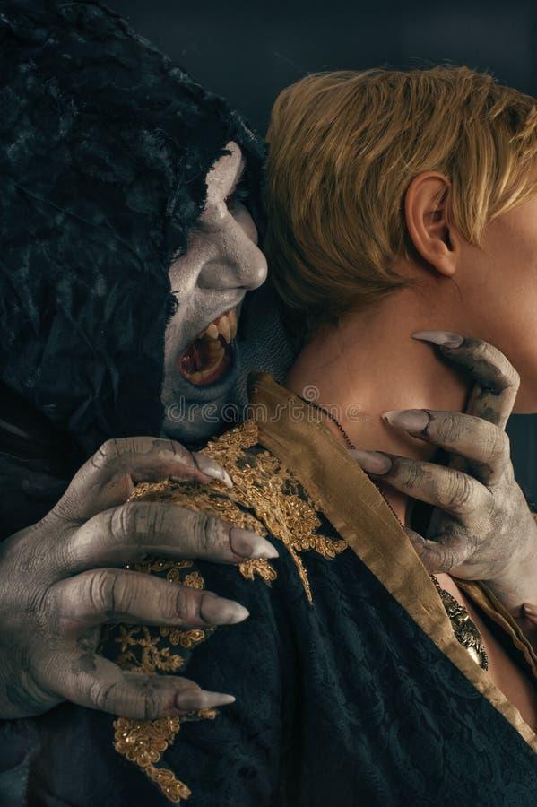 Alter Monstervampirsdämon beißt einen Frauenhals Halloween fant stockbilder