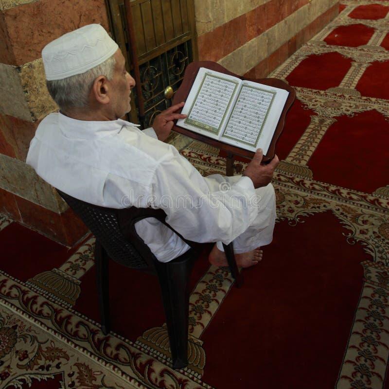 Alter moslemischer Mannlesungsquran in einer Moschee stockfotografie