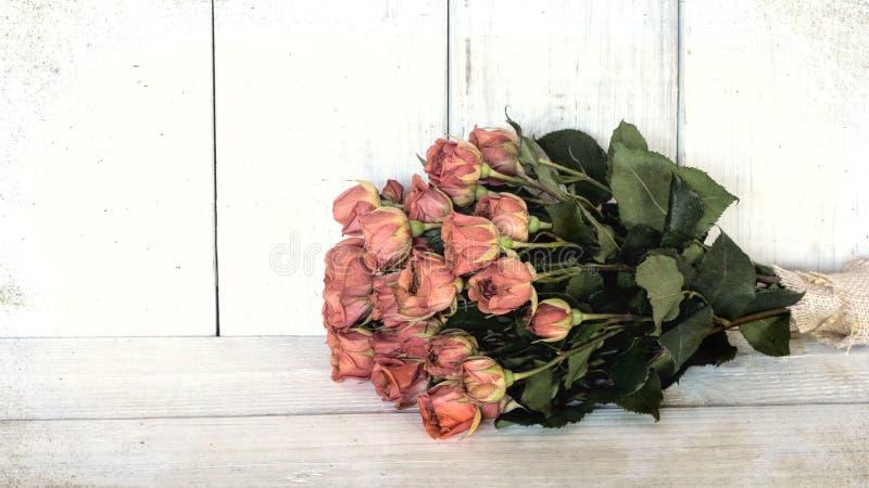 Alter Pfirsich-Rosen-Blumenstrauß mit an einer Tabelle des weißen Brettes und gegen einen beunruhigten shiplap Bretthintergrund E lizenzfreie stockbilder
