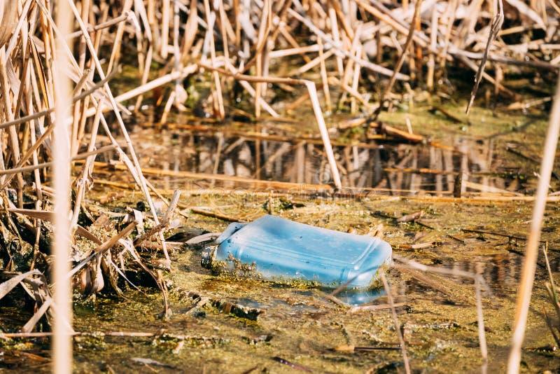 Alter Plastikkanister schwimmt in Wasser des Sumpfs oder des Teichs Benutztes leeres Verpackungsmaterial gelassen im Wasser Eco-K stockbilder