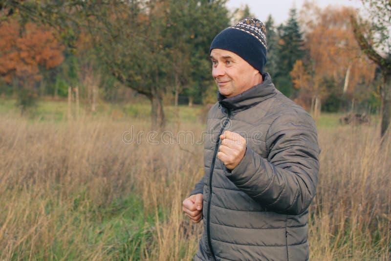 Alter positiver Mann in einem Hut mit einem Lächeln spielt Sport, läuft in der Natur, das Konzept eines gesunden Lebensstils und  lizenzfreie stockfotos