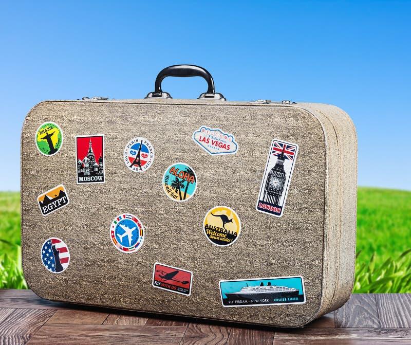 Alter Reisekoffer auf Hintergrund mit Rasenfläche lizenzfreie stockbilder