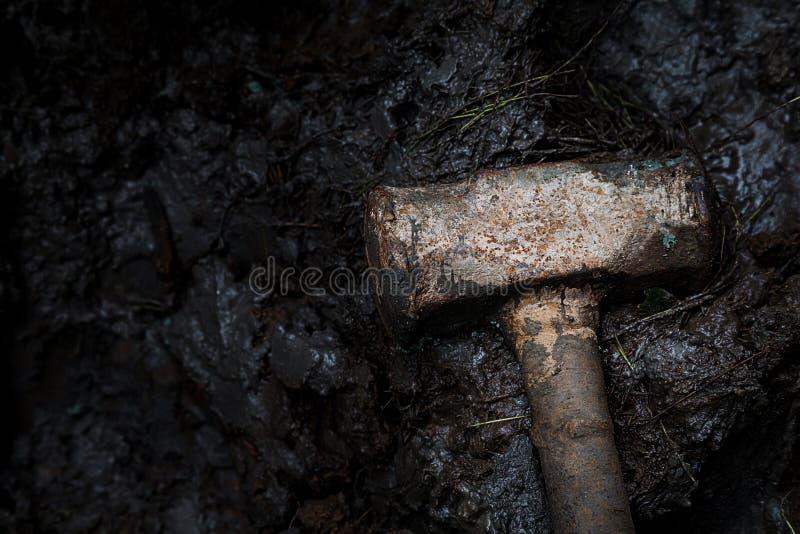 Alter rostiger Eisenbauhammer auf dem Schlamm, der drastischen Fotografie und der zurückhaltenden Fotografie Bauwerkzeug- und -ve stockbilder