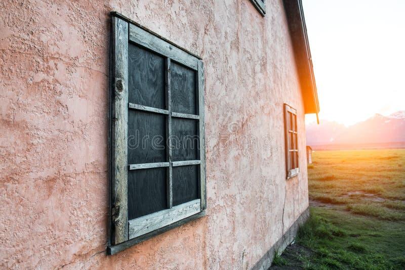Alter rostiger Holzrahmen auf Stein gemalter rosa Wand auf Gebirgshaus zur Sonnenuntergangzeit lizenzfreies stockbild