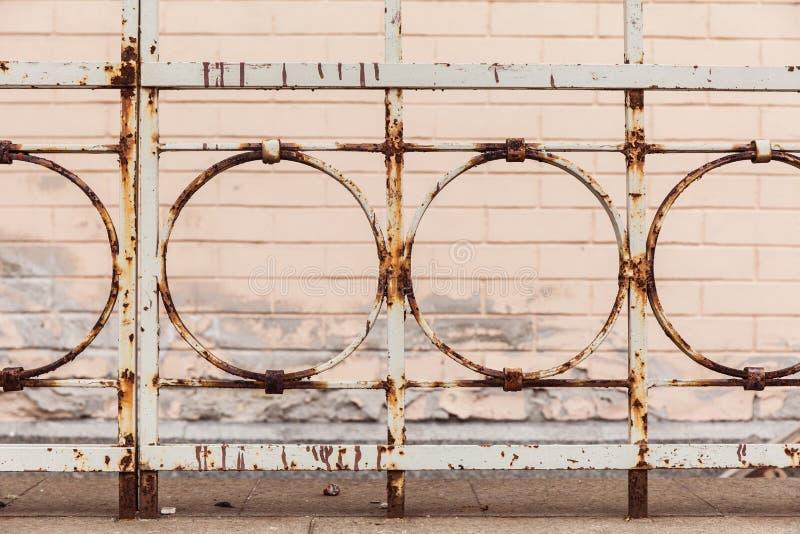Alter rostiger Zaun auf dem Hintergrund eines Backsteinhauses lizenzfreie abbildung