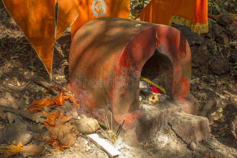 Alter roter schäbiger hindischer Tempel mit orange Flaggen und Angebote im Wald lizenzfreies stockbild