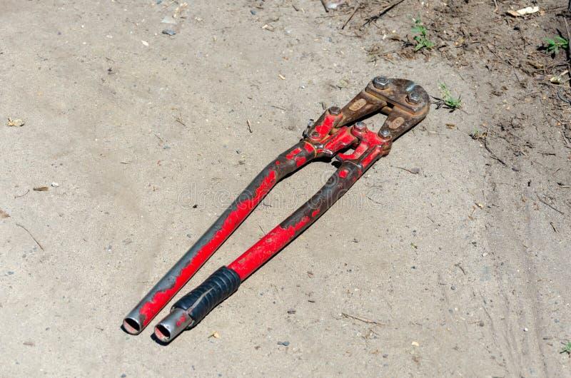 Alter roter Schneider der Draufsicht für Draht oder Stahlstangen auf dem Land stockbild