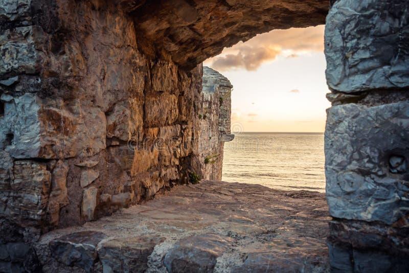 Alter Ruinenhintergrund mit szenischem Sonnenuntergang über Meer durch altes Schlossfenster mit drastischer Himmel- und Perspekti stockfotografie