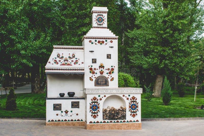 Alter, alter russischer Ofen Weiß und Stein mit Zeichnungen und Malereien von Verzierungen lizenzfreies stockfoto