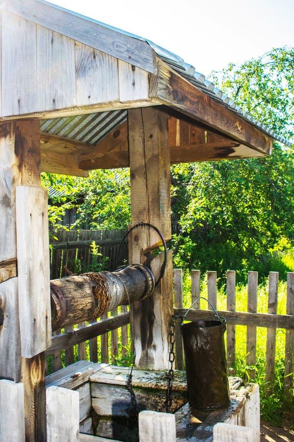 Alter rustikaler h?lzerner Brunnen mit Eimer Dorf gut unter dem Dach mit einer Metallkette an einem bew?lkten Herbsttag, Russland lizenzfreie stockfotografie