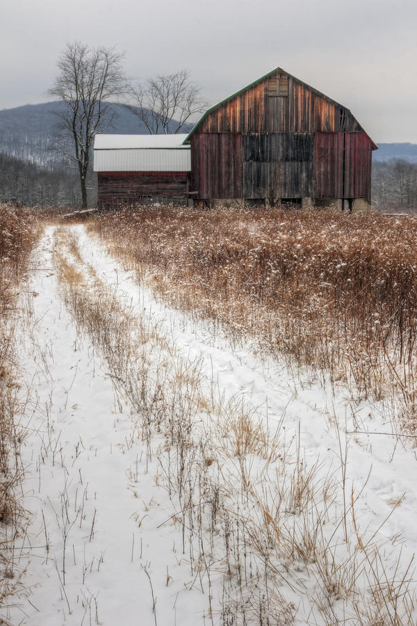 Alter rustikaler Stall und Schnee stockfoto