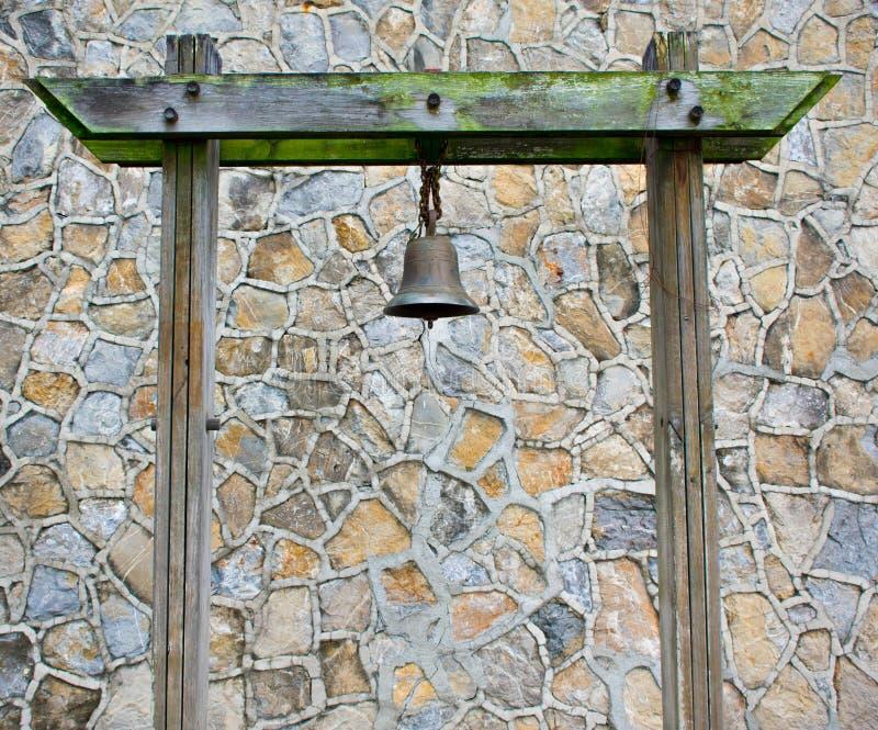 Alter Rusty Bronze Metal Bell Hanged auf einer grünen moosigen hölzernen Säule in einer Steinmuster-Wand stockfotografie