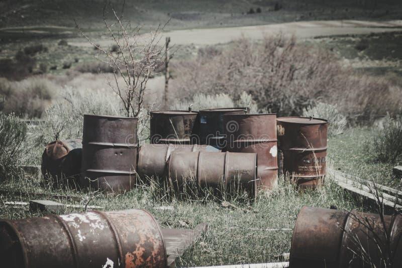 Alter Rusty Steel Drum Barrels Sitting auf einem Gebiet lizenzfreie stockbilder