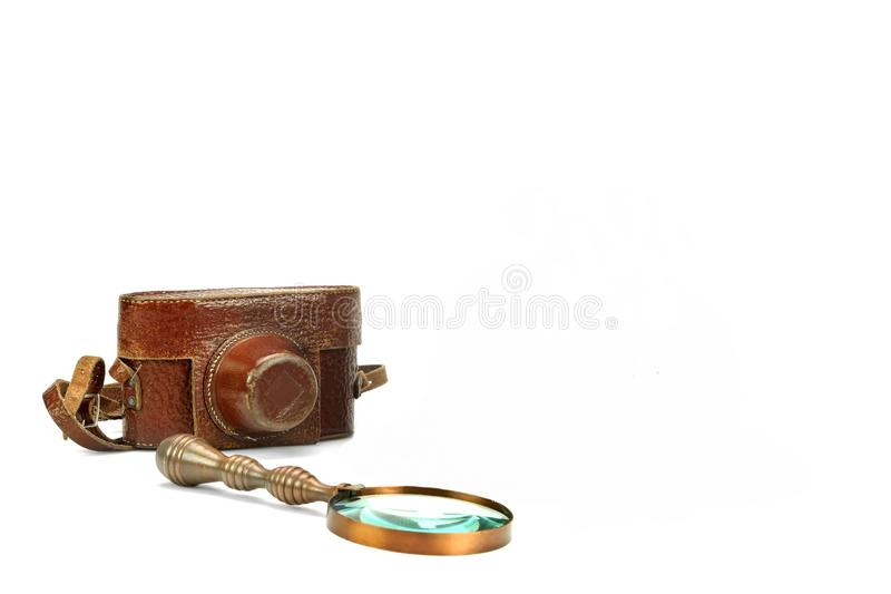 Alter schäbiger SLR-Foto-Kamera-Kasten und Lupe lokalisiert stockbilder