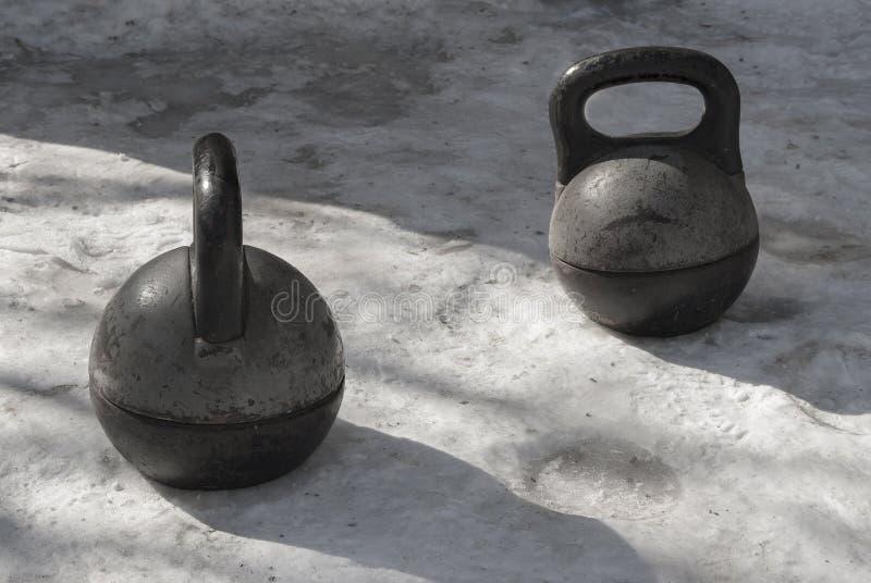 Alter schwarzer schwerer kettlebell zwei Stand auf dem Schnee stockbild
