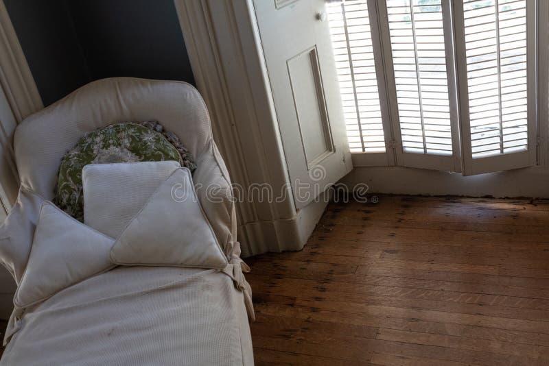Alter slipcovered Daybed neben einem Fensterläden geschlossenen Fenster, antike Holzfußböden, Kopienraum stockfotos