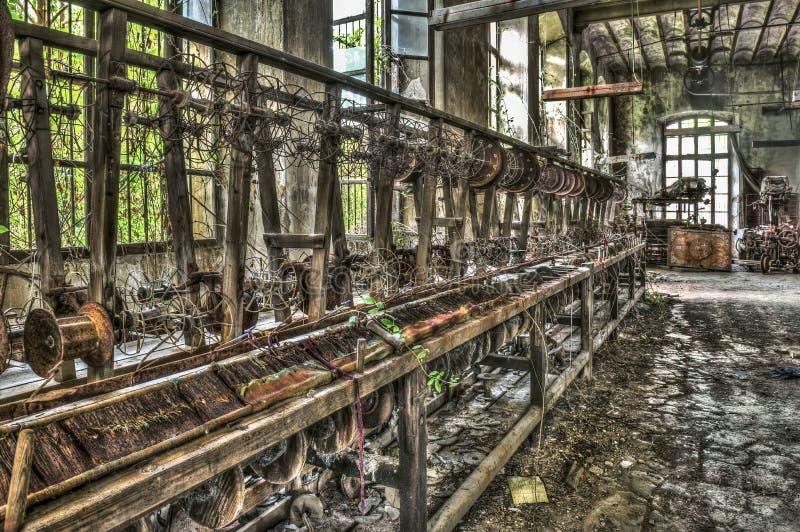 Alter spinnender Webstuhl und spinnende Maschinerie an einer verlassenen Fabrik stockfoto