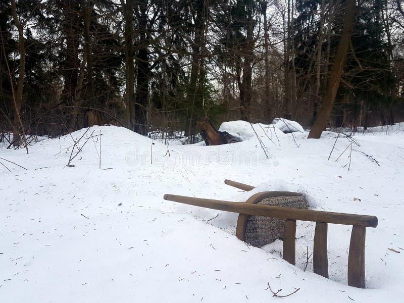 Alter Stuhl mit der Gewebepolsterung eingefroren im Wald im weißen Schnee lizenzfreies stockfoto