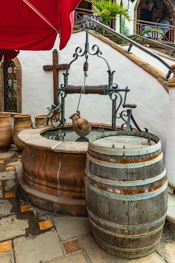 Alter Töpferwarenkrug, der an einem Seil über einem rustikalen Brunnen hängen und ein Weinleseeichenweinfaß in einer Weinstöcke v lizenzfreies stockfoto