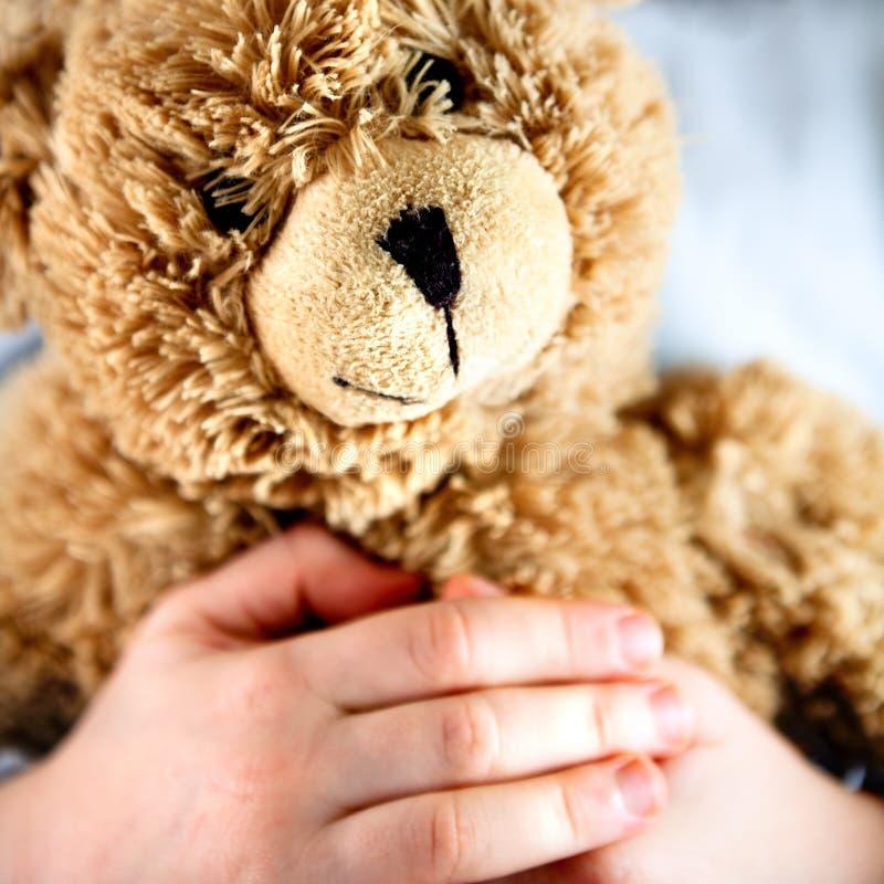 Alter Teddybär in den Händen eines Kindes lizenzfreie stockfotos