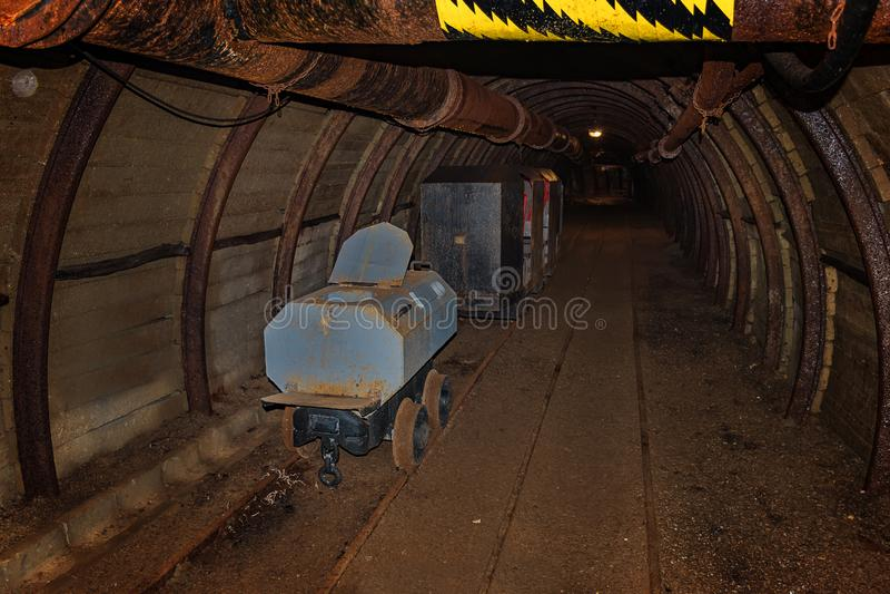Alter Toilettenlastwagen- und -metallbergwerkzug im Bergwerktunnel mit hölzernem Zimmern lizenzfreie stockfotografie