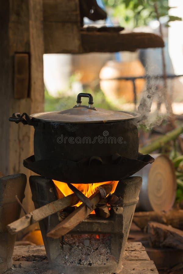Alter Topf, der auf hölzernem brennendem Ofen steht lizenzfreie stockfotos