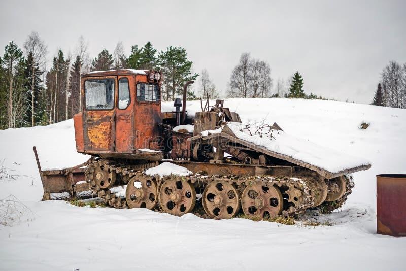 Alter Traktor steht auf Schnee im Winter stockfotos