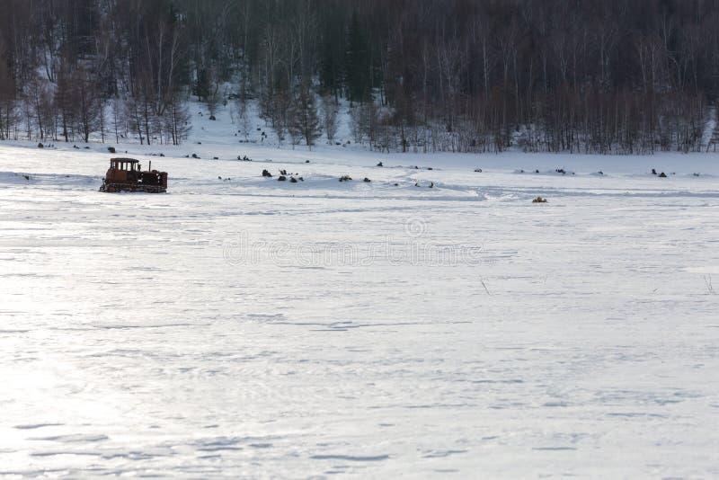 Alter Traktor unter dem Schnee stockbild