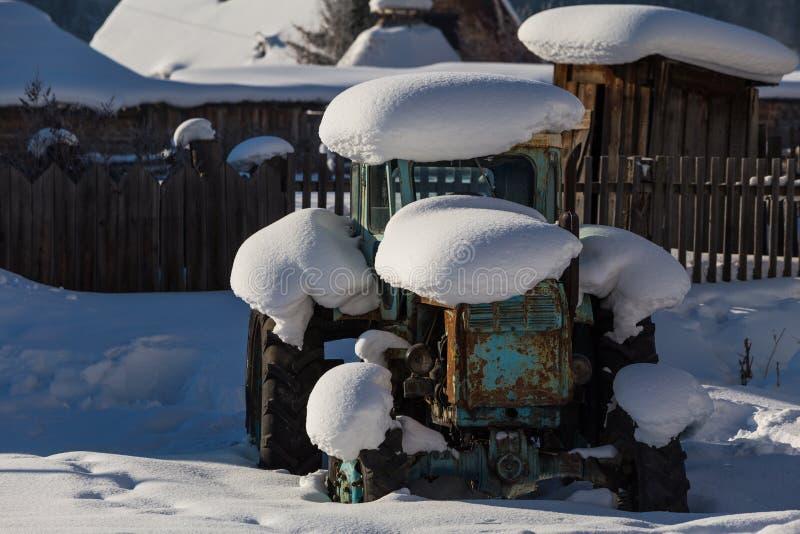 Alter Traktor unter dem Schnee stockbilder