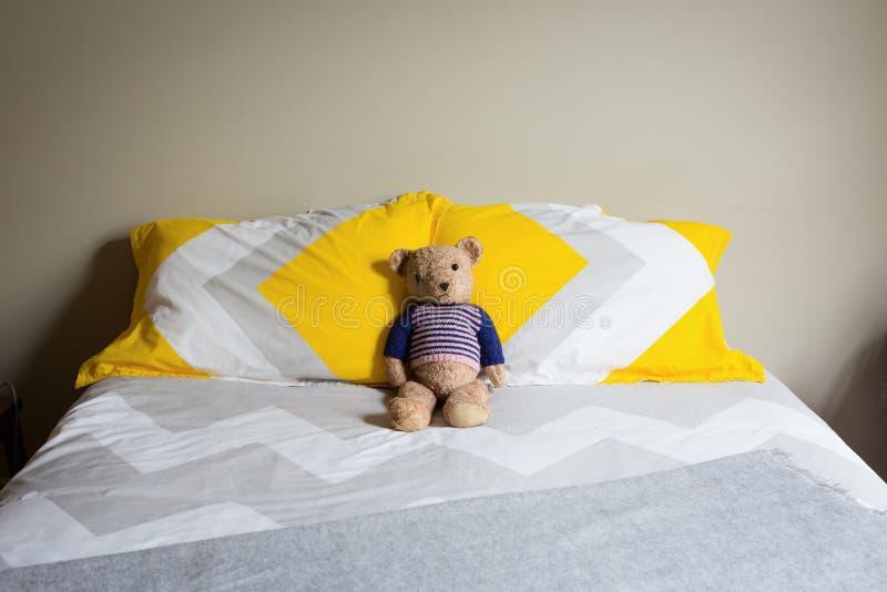 Alter trauriger schauender Teddybär auf einem Doppelbett stockfoto