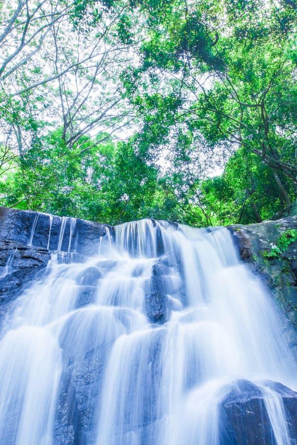 Alter tropischer Wasserfall, der steil auf Schichten von in Sommer fällt stockfotografie