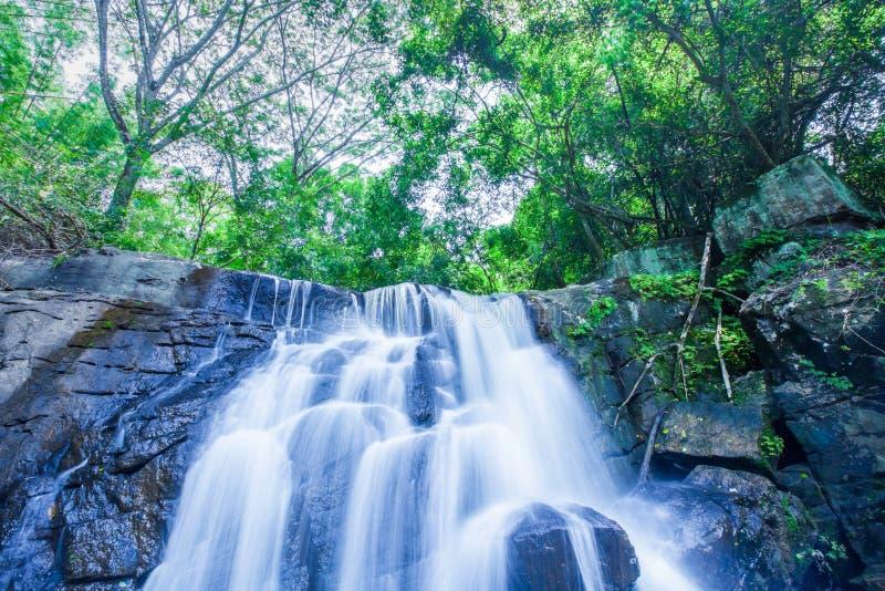 Alter tropischer Wasserfall, der steil auf Schichten von in Sommer fällt lizenzfreie stockfotos