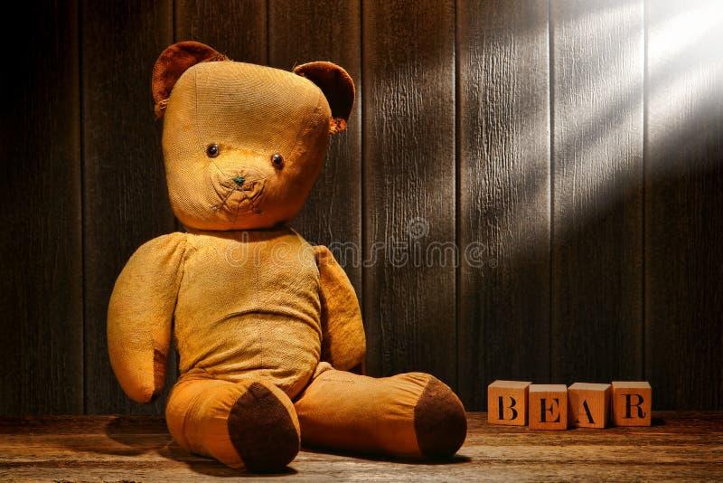 Alter und benutzter Weinlese-Teddybär-Spielzeug-Bär in gealtertem Dachboden lizenzfreie stockfotografie