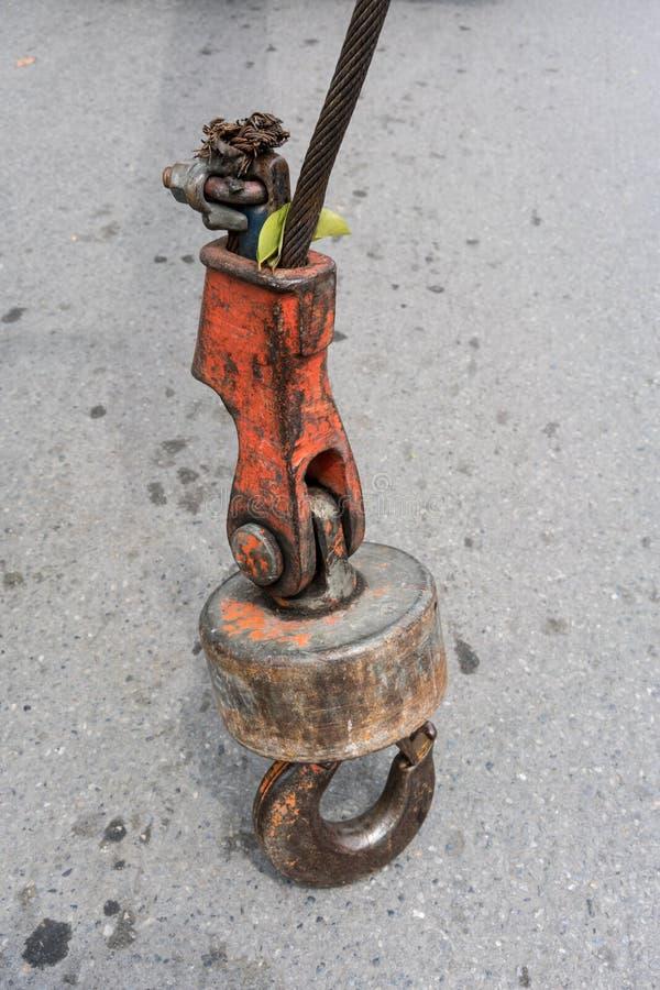 Alter und rostiger Eisenhaken, der auf konkretem Boden steht lizenzfreie stockfotos