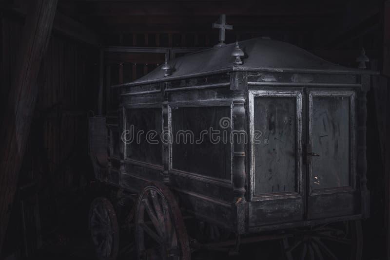Alter und staubiger Begräbnis- Pferdewagen oder -leichenwagen verließen in einer Scheune lizenzfreies stockbild
