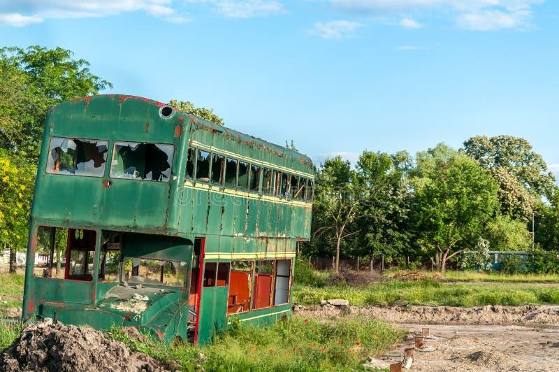 Alter verlassener grüner Doppeldeckerbus mit dem defekten und zerbrochenen Fensterglas, beschädigt und verließ zum Rost stockbilder