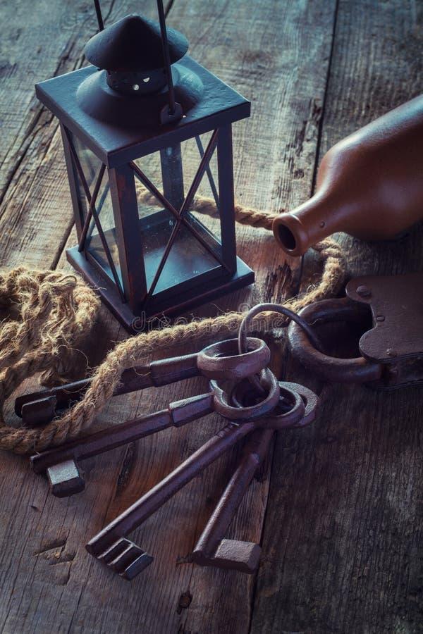 Alter Verschluss mit Schlüsseln, Weinleselampe, Flasche vom Lehm und Seil lizenzfreie stockfotografie