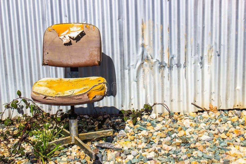 Alter verwitterter Stuhl auf außerhalb Gebäude stockfotografie