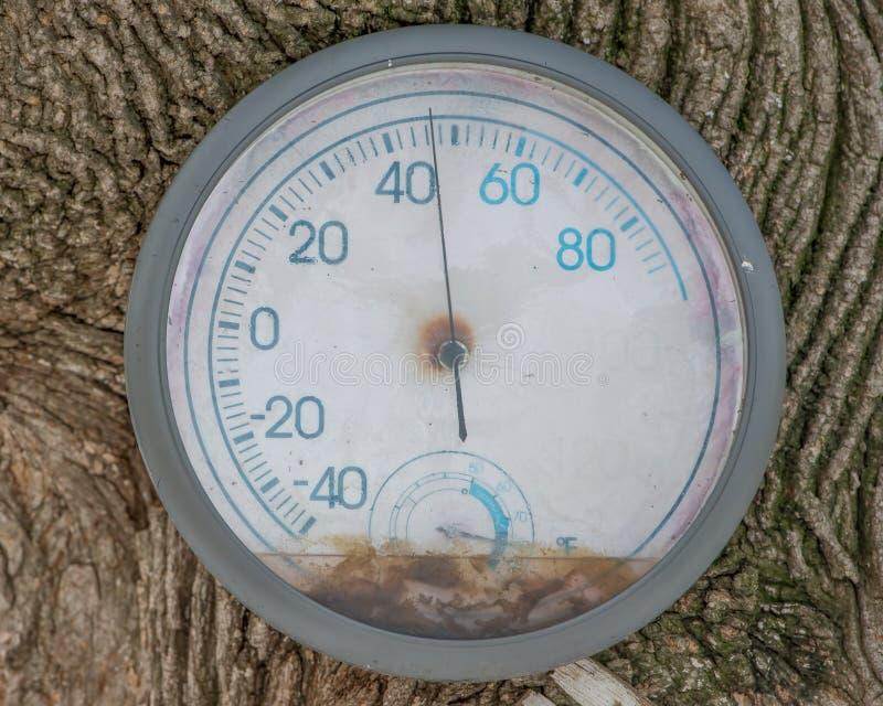 Alter verwitterter Thermometer draußen und gab zu einem Baum - ungefähr 45 Grad heraus bekannt lizenzfreie stockbilder