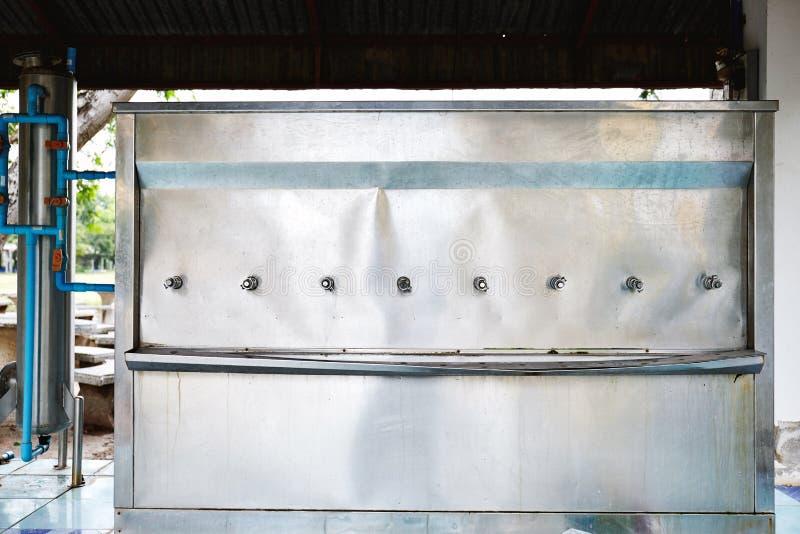 Alter Wasserbehälter gemacht vom Edelstahl in der Schule für Studenten stockfotografie