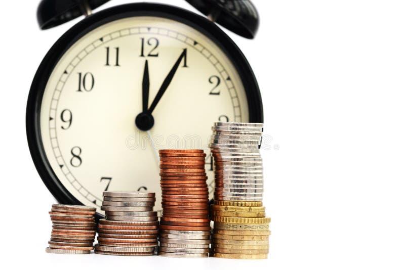 Alter Wecker und Stapel Münzen, Zeit-Leistungsfähigkeits-Konzept lizenzfreies stockfoto