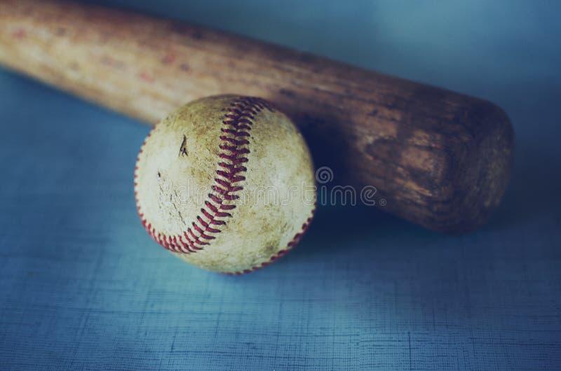 Alter Weinlesebaseball und -schläger gegen blauen Beschaffenheitshintergrund stockbild