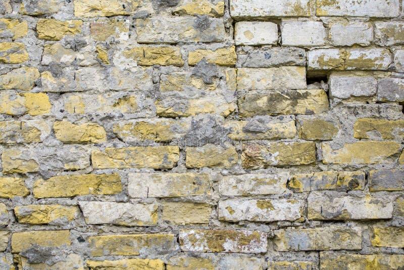 Alter Ziegelstein ruinierte verwitterten konkreten Zement des Schmutzes der Wand beige Oberfläche mit Löchern, Abnutzung und Zers lizenzfreies stockfoto