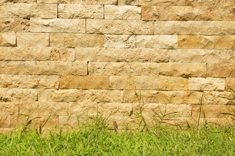 Alter Ziegelsteinsteinwandhintergrund mit Gras lizenzfreies stockfoto